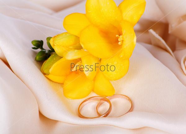 Фотография на тему Обручальные кольца и фрезии на ткани