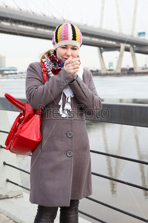 Фотография на тему Замерзшая женщина в шарфе стоит на набережной