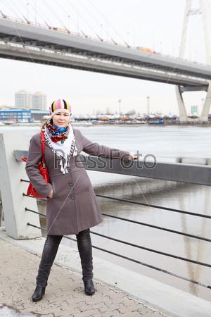 Улыбающаяся женщина в шарфе стоит на набережной