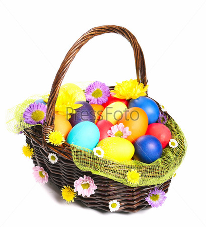 Разноцветные пасхальные яйца в плетеной корзине изолированы на белом фоне