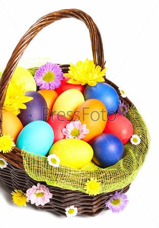 Фотография на тему Разноцветные пасхальные яйца в плетеной корзине изолированы на белом фоне