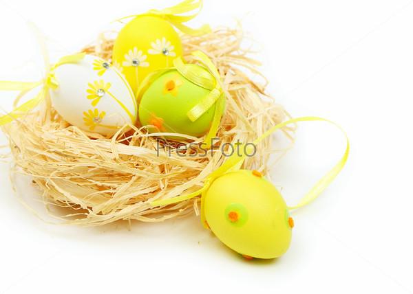 Разноцветные пасхальные яйца в гнезде изолированы на белом фоне