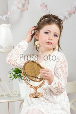 Фотография на тему Красивая маленькая девочка смотрится в небольшое зеркало