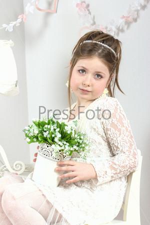 Красивая маленькая девочка с цветами в горшочке