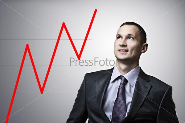 Фотография на тему Красивый бизнесмен с финансовым графиком на сером фоне