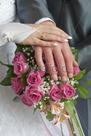 Руки молодоженов с обручальными кольцами на свадебном букете