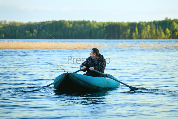 Рыбак в резиновой лодке на озере