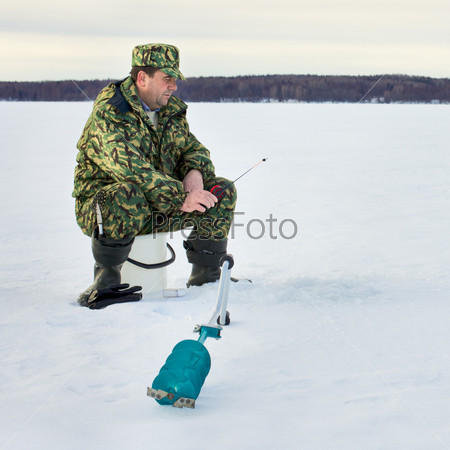 Человек рыбачит на озере зимой