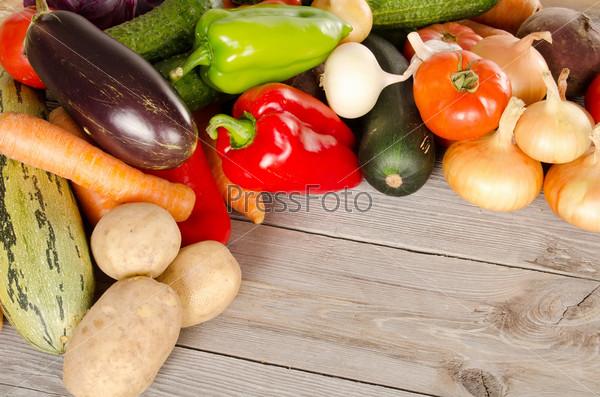 Ассортимент свежих овощей на деревянном фоне