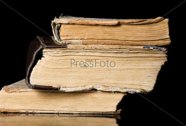 Стопка старых книг, изолированная на черном фоне