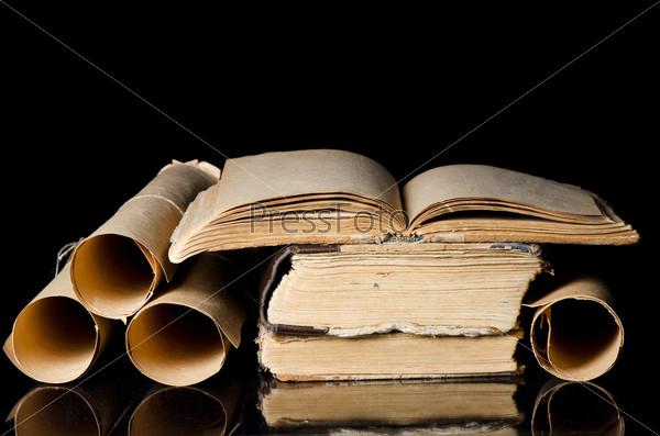 Стопка старых книг и свитки, изолированные на черном фоне