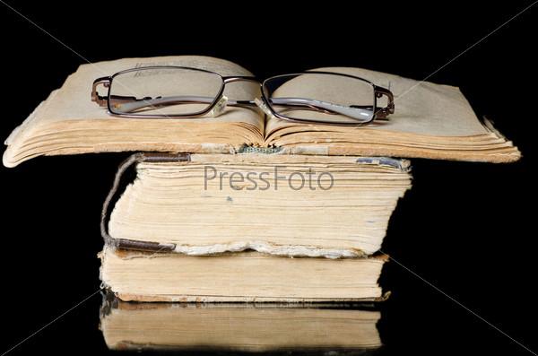 Стопка старых книг и очки, изолированные на чернм фоне