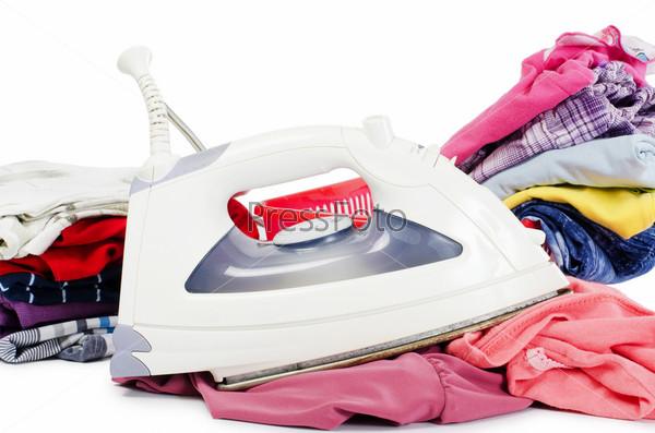 Фотография на тему Куча чистой одежды и утюг