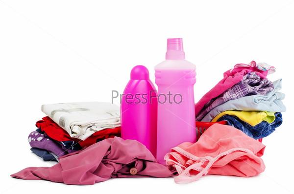 Куча чистой одежды и моющие средства