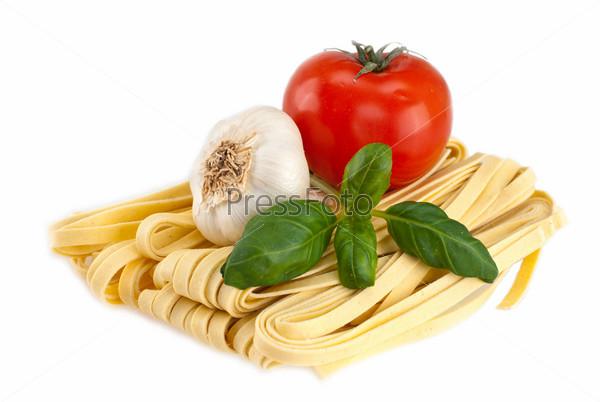 Спагетти, чеснок, помидор и базилик на белом фоне