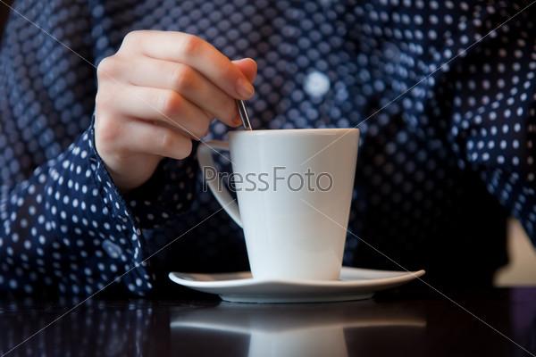 Женская рука тщательно размешивает кофе в белой чашке
