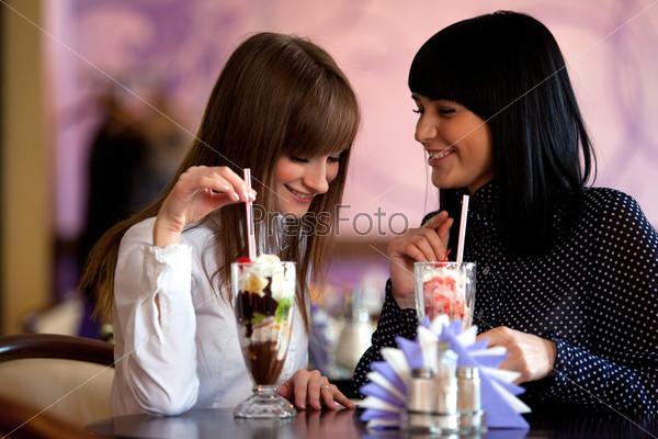 Две женщины с коктейлями на столе