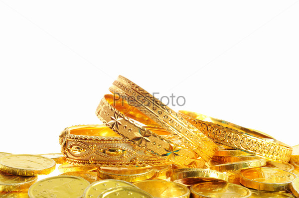Золотые монеты и браслеты на белом фоне