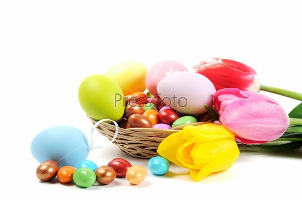 Крашеные пасхальные яйца и тюльпаны на белом фоне