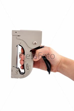 Фотография на тему Канцелярский пистолет для скрепок в руке на белом фоне