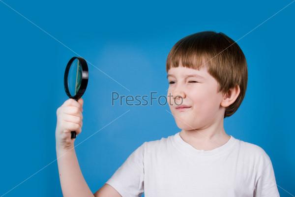 Фотография на тему Улыбающийся мальчик смотрит через увеличительное стекло на синем фоне
