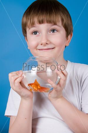 Мальчик держит аквариум с золотой рыбкой на синем фоне