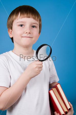 Улыбающийся мальчик с увеличительным стеклом и книгами на синем фоне