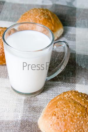 Стакан молока и булочки на серой скатерти