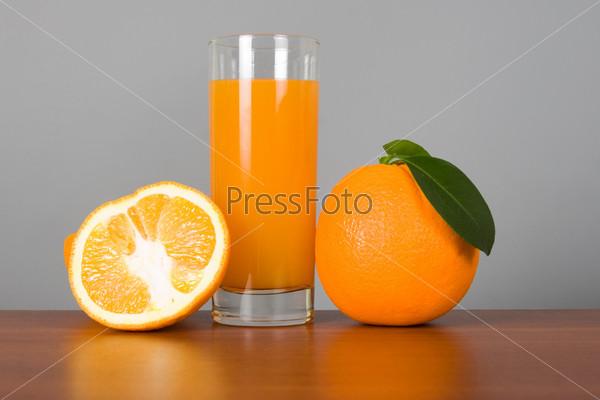 Апельсины и сок в стакане на столе