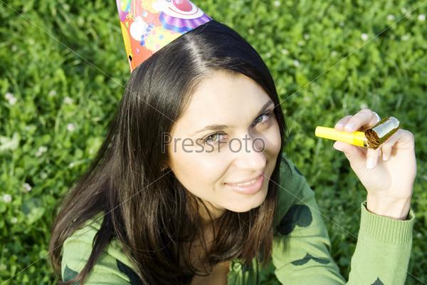 Фотография на тему Красивая девушка в праздничном колпаке со свистком в руке сидит на траве