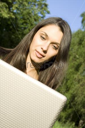 Фотография на тему Молодая женщина с ноутбуком в парке