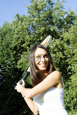 Молодая женщина играет в теннис на свежем воздухе