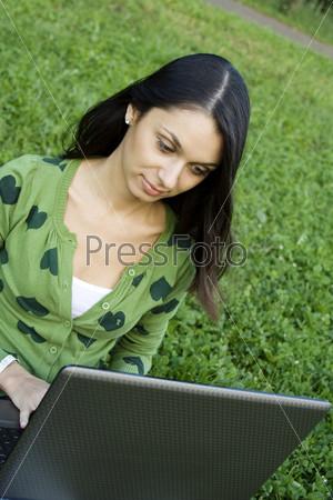 Молодая женщина с ноутбуком сидит на траве в парке