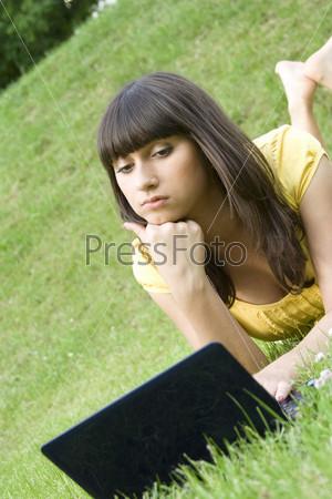 Молодая женщина с ноутбуком лежит на газоне в парке