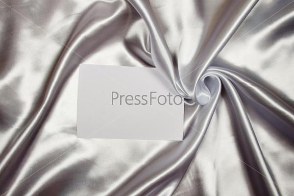 Белая поздравительная или пригласительная карточка на шелковом фоне