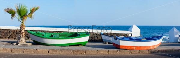 Фотография на тему Две лодки и пальмы на побережье. Панорама. Лансароте, Канарские острова, Испания