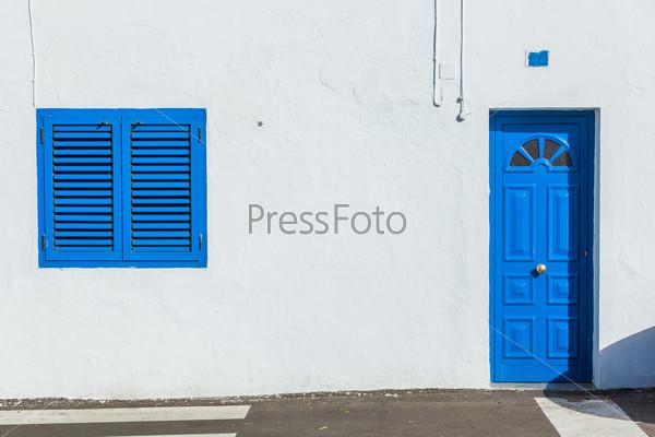 Синие деревянные колониальное окно и дверь на стене