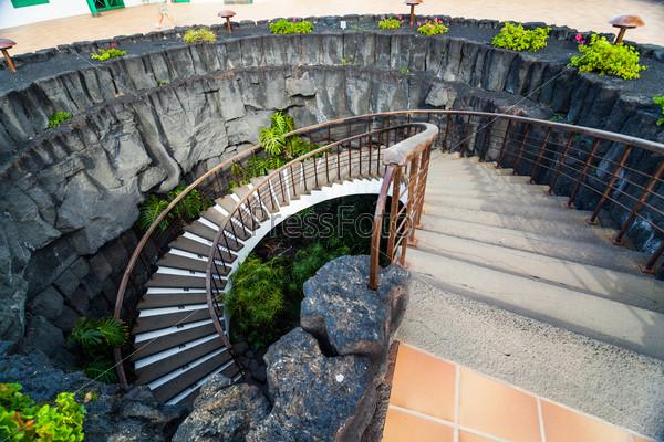 Каменная винтовая лестница с цветами в современном интерьере