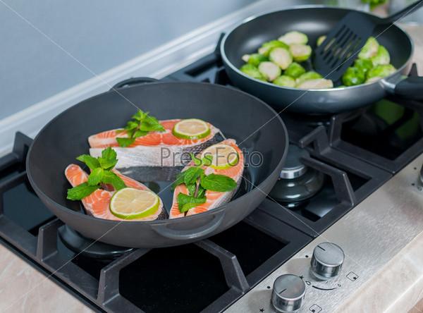 Овощи готовятся в черных сковородах на кухне