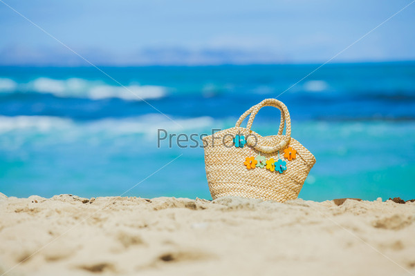 Соломенная сумка с цветами на экзотическом песчаном пляже
