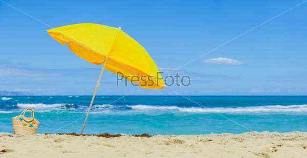 Соломенная сумка с цветами и желтый пляжный зонтик на экзотическом песчаном пляже