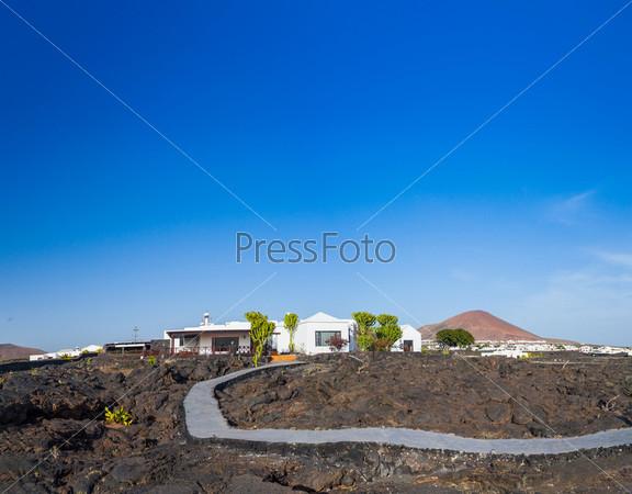 Панорама типичного коттеджа и дороги, построенных на вулканической лаве. Лансароте, Канарские острова