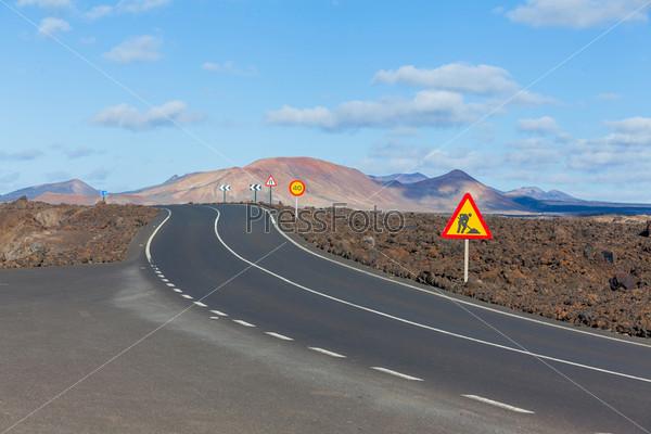 Пустынная дорога, проходящая по вулканической поверхности. Панорама. Лансароте, Канарские острова, Испания