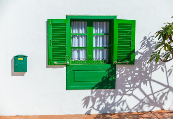 Зеленое деревянное колониальное окно на стене дома