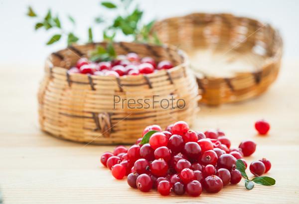 Свежая красная клюква с листьями в корзине