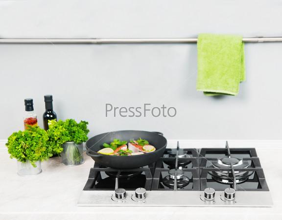 Красная рыба с мятой и лимоном на черной сковороде на кухне