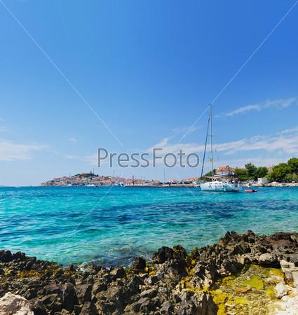 Панорамный вид Далматинского побережья с яхтой на море и городом Ровинь в Хорватии