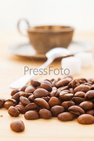 Кофе в зернах с чашечкой кофе
