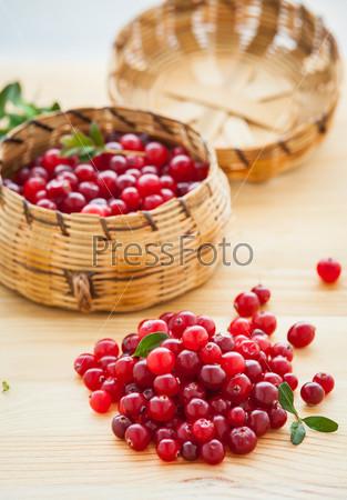 Фотография на тему Свежая красная клюква с листьями в корзине