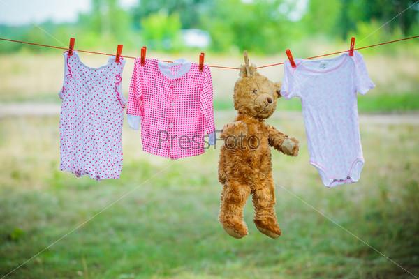 Детская одежда и плюшевый мишка на веревка для белья